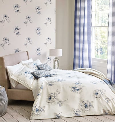 Sanderson 'Rosa' Bedding: A bold blue and grey hand-drawn rose pattern on a cream background.