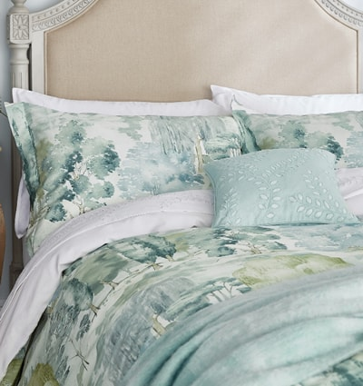 Sanderson 'Waterperry' Bedding: A striking bedding design featuring a detailed, hand-painted woodland scene formed of several different breeds of tree.